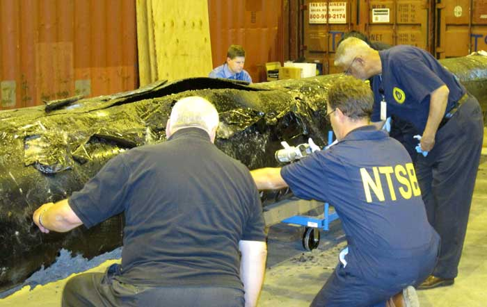 NTSB staff examine ruptured pipe