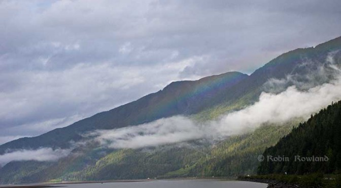 A rainbow hugs the mountains near the Telegraph Point rest area on the Skeena River between Terrace and Prince Rupert, Sept. 29, 2014.  Traffic hugs the narrow corridor between the mountains and the river (Robin Rowland/Northwest Coast Energy News)